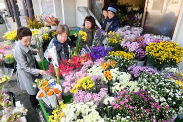 彼岸の入りで墓前に供える花を選ぶ市民ら=18日、盛岡市本町通・千葉商店
