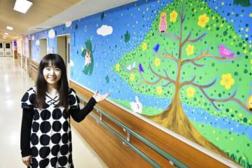 十全ユリノキ病院の廊下を彩る巨大壁画に手をかざす作者のSEIKOさん