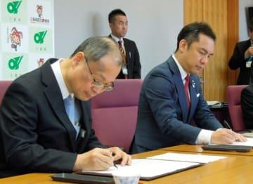 【協定書に署名する高橋会長(左)と鈴木知事=三重県庁で】
