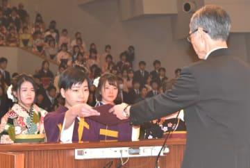 【清水学長(右)から学位記を受け取る卒業生=伊勢市神田久志本町の皇學館大学で】