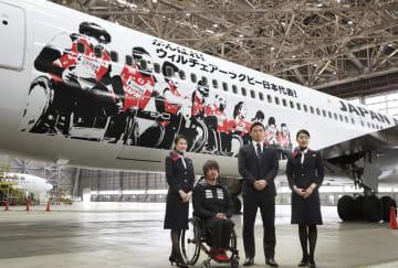 車いすラグビー日本代表の選手らがデザインされた日航の特別機と、記念写真に納まる池崎大輔選手(左から2人目)と五郎丸歩選手(同3人目)=19日午前、羽田空港