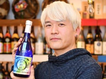 新デザインを手掛けた山川酒造の「珊瑚礁5年古酒35度」を持つ岡山進矢さん=東京・銀座の沖縄料理店「島どうふ」