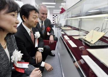 杉原ビザを見つめる(左から)孫の杉原まどかさん、千弘さん。右はジョージ・ブルマンさん=19日午後、東京都中央区
