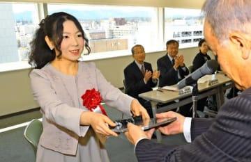 第23回県美術海外留学賞授賞式で町川社長から記念の盾を受ける奥野さん(左)=19日午前、宮崎市・宮日会館