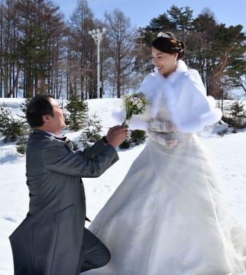 雪景色の中、カメラの前で新婦・楊慧芝さんに花束を手渡すポーズを取る新郎・郭偉賢さん