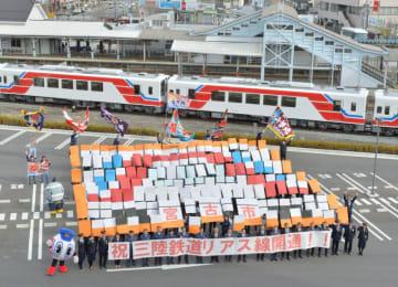 163人の人文字で三陸鉄道の車両を表現する市職員ら。23日のリアス線開通へ機運を高めた=19日、宮古市宮町