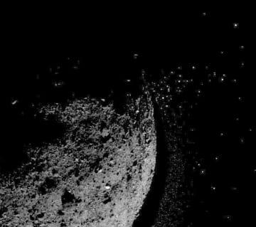 小惑星ベンヌ(左)の表面から噴き飛ぶかけら。NASAの探査機オシリス・レックスが1月に捉えた(NASA提供・共同)