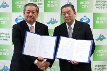 協定書に調印して握手を交わす林代表執行役(左)と金澤市長=雲仙市役所
