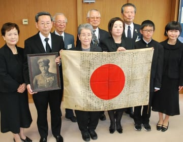 時田敏さんの日章旗を受け取った遺族(前列)ら=19日、袖ケ浦市役所