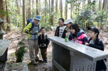 野上英二さん(左)から妙見上宮跡の説明を聞く子ども記者たち=八代市