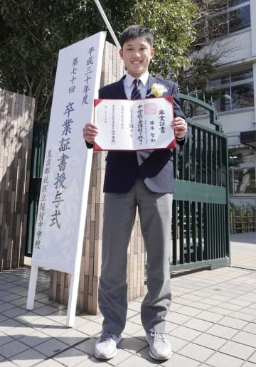 東京・稲付中の正門前で、卒業証書を手にする卓球男子の張本智和選手=20日午後、東京都北区