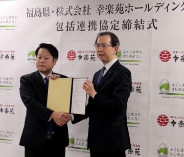 協定書を掲げる新井田社長(左)と内堀知事