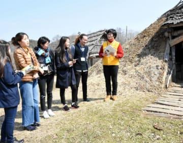 御所野遺跡を巡りガイドの説明を受ける留学生