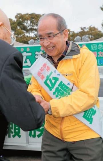 支持者と握手をする広瀬勝貞候補=21日午前、大分市の大分城址公園