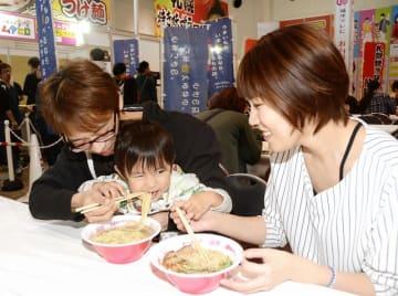 ラーメンを食べ比べする親子=3月20日、福井県福井市の福井県産業会館
