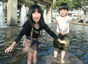県内各地で気温が上昇。水遊びを楽しむ子どもら=21日午後3時、大分市中央町の若草公園
