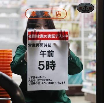 24時間営業見直しに向けた実験を実施しているセブン―イレブンの店舗で、営業再開時刻についてのお知らせを張る店員=22日未明、東京都足立区