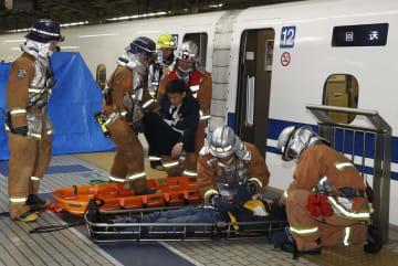 JR東海などのテロ対策訓練で、消防隊員に運び出される人たち=22日未明、新大阪駅