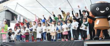 大型観光キャンペーンのPR用振り付けを披露して開幕を宣言する園児や観光関係者