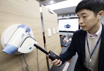 20日、ソウルの韓国警察庁で盗撮用の小型カメラが設置されたドライヤーの固定台を調べる捜査関係者(聯合=共同)