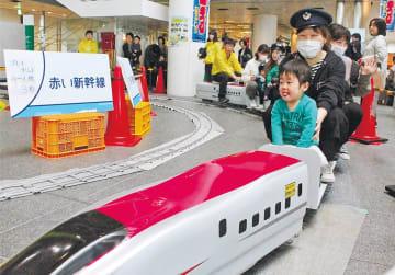 ミニ新幹線に乗る親子連れ