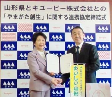 包括連携協定締結式で握手する吉村美栄子・山形県知事(左)と長南収・キユーピー 代表取締役 社長執行役員