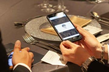 「まるる」のサービスでは、披露宴の席札に印刷されたQRコードをスマートフォンで読み取ると新郎新婦からの個別メッセージを見られる