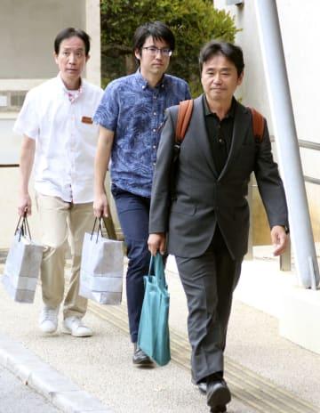 福岡高裁那覇支部に向かう沖縄県側の弁護士(右)と県職員=22日午後、那覇市