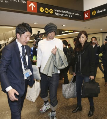 22日、米シアトルの空港に到着したイチロー元選手(中央)。右は弓子夫人(共同)