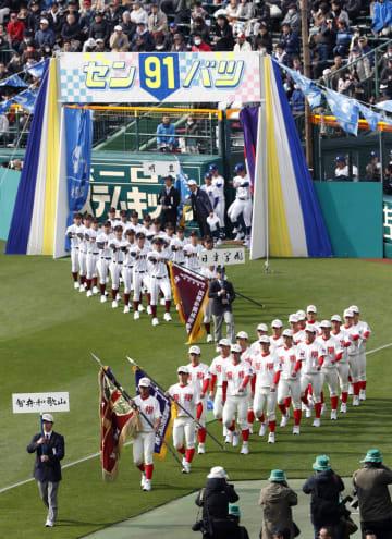 第91回選抜高校野球大会の開会式で入場行進する智弁和歌山(手前)と日章学園の選手ら=23日午前、甲子園球場