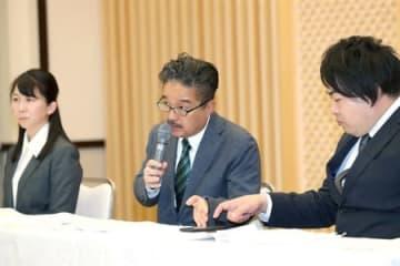 山口真帆さんが更新したSNSを確認しながら質問に答える松村匠AKS取締役(中央)=22日、新潟市中央区