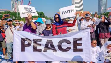 マレーシア・クアラルンプールで開かれた集会で「PEACE(平和)」と書かれた横断幕を掲げる参加者=23日(共同)