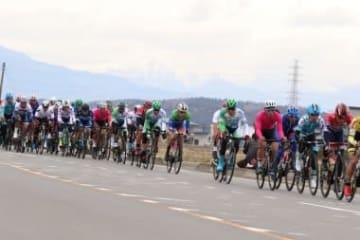 雪山をバックに選手たちがロードレース初日を走る