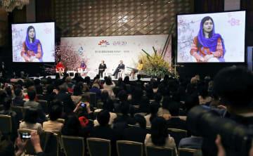 国際女性会議のパネルディスカッション。モニター画面は発言するノーベル平和賞受賞者のマララ・ユスフザイさん=23日、東京都内のホテル