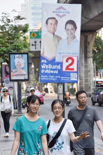 23日、タイ下院総選挙を翌日に控え、候補者のポスターが並ぶバンコク中心部を歩く人々(共同)