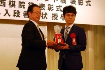 山陽新聞社の仮谷編集局長からトロフィーを受け取る余第一位(右)