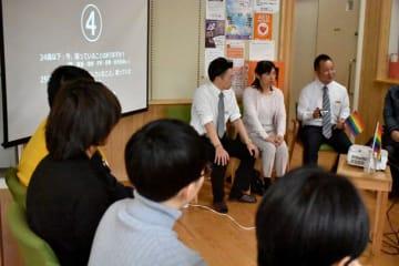 山田代表(右奥)らと語り合う10~20代の県内当事者たち(手前)=23日午前、宮崎市