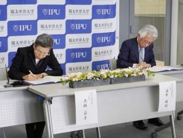 協定書に署名する大橋学長(左)と酒井会長
