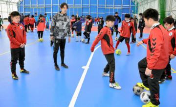 サッカー少年に技を教える岡部さん(左から2人目)