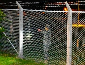 キャンプ瑞慶覧のフェンス沿いをパトロールする米兵=24日午後10時すぎ、宜野湾市伊佐