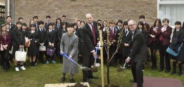 英南西部ブリストルに近いキャサリン・レディー・バークレーズ校で、桜の植樹式を行う同校の関係者と山梨県立日川高の小尾美保教諭(前列左)=18日(共同)