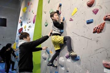石松大晟さん(左)の指導を受けながらボルダリングを体験する参加者=23日午後、小鹿野町両神薄の町両神体育館