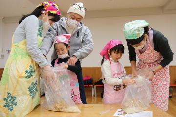 玄米こうじ、塩、煮大豆を混ぜ合わせてみそを仕込む参加者