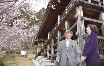 日航機事故犠牲者を追悼し植えた桜の下で語り合う黒沢完一さん(左)と鷲尾博子さん=25日午後、大津市の石山寺