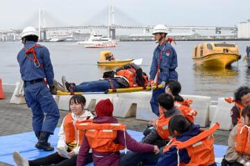 訓練で、超大型客船から救命艇(右奥)で避難した乗客役=横浜港大さん橋ふ頭