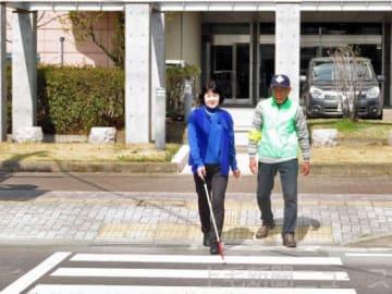 白杖を使い横断歩道を渡る女性と支援するガイドヘルパー=前橋市新前橋町