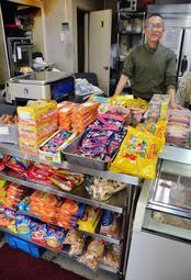 店を経営する竹本悦夫さん。店内には日本のスーパーでは手に入りづらい食品が並ぶ=神戸市東灘区深江南町4