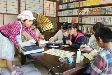 読書やデザートを楽しむ子どもたちの後ろにはさまざまなジャンルの蔵書がずらり
