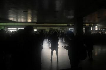 25日、ベネズエラの首都カラカスで、停電した国際空港を利用する人々(ロイター=共同)