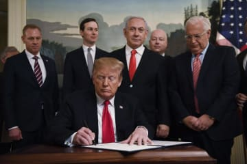 25日、米ホワイトハウスで、ゴラン高原のイスラエル主権を認める宣言に署名するトランプ大統領(AP=共同)